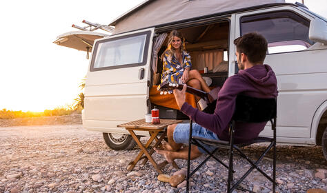 Couple with their camper van on a beach at sunset